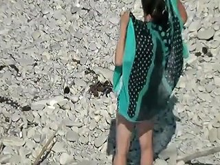 Mature Woman Sunbathing In Rocky Beach